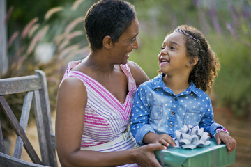 Happy young girl smiling at her mother as she receives a birthday present.