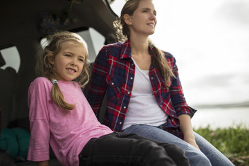 Little girl enjoys sitting in the back of the car with her mother and looking at the countryside view.