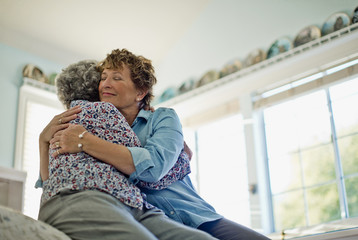 Mature woman gently smiles as she embraces her elderly mother as they sit on the edge of a comfortable bed.