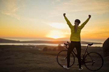 Young woman raising her arms in victory after cycling to the top of a hill.