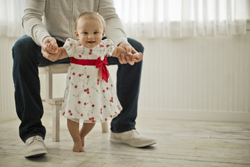 Portrait of a smiling baby girl taking her first steps assisted by her father.