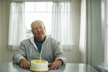 Portrait of a senior man sitting in front of a birthday cake.