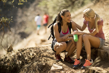 Two smiling young women taking a break while hiking.
