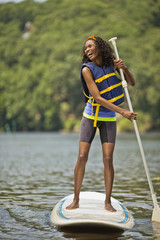 Smiling young woman having fun on a paddleboard.
