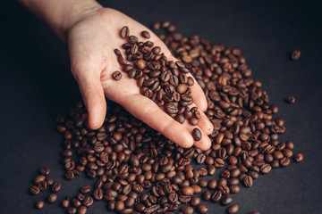 coffee beans in hand and dark background