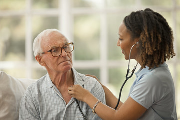 Contemplative senior man having his heartbeat listened to by a female nurse.