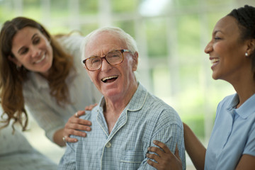 Portrait of a laughing senior man being comforted by a female nurse and his adult daughter while wearing pajamas.