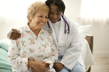 Smiling senior woman sitting next to a female doctor on the edge of a bed.