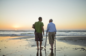 Senior man with a walking aid on the beach with his son and grandchild.