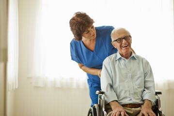 Portrait of a smiling senior man being comforted by a nurse while sitting in a wheelchair.