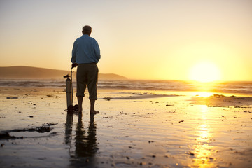 Senior man standing on a beach with his oxygen tank at sunset.