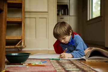 Young boy intently coloring in with crayons.
