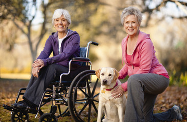 Portrait of two smiling women in a park with their dog.