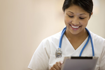 Portrait of young female nurse writing on a clipboard.