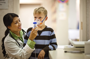 Doctor puts oxygen mask on young boy.