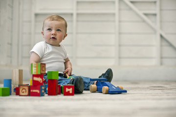 Baby boy playing with blocks on the floor.