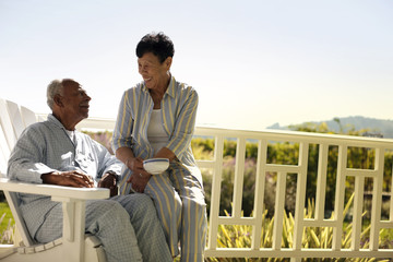 Senior couple sitting on their verandah in pajamas.
