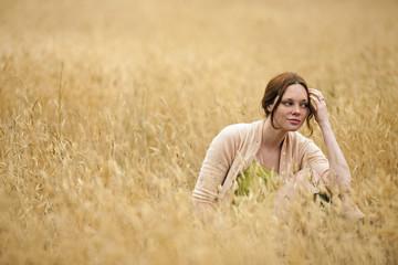 Teenage girl enjoying sitting in wheat field.