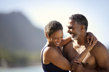 Mid adult couple standing with their arms around each other on a beach.