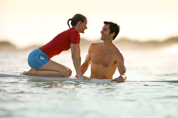 Mid-adult woman facing her boyfriend as she learns how to surf.