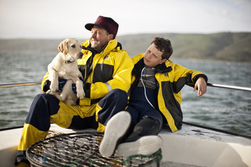 Father sitting with son and holding dog, as they take a break on fishing boat.