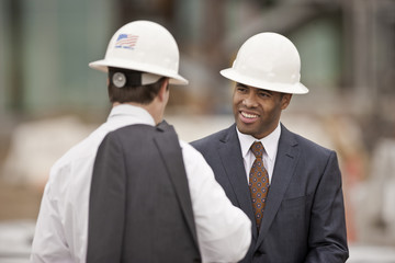 Two young engineers having a business discussion while wearing suits and hardhats.