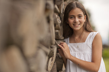 Smiling girl leaning on log fence.