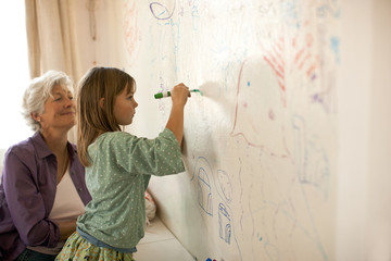 Mature woman happily watches her young granddaughter write on a bedroom mural wall with a felt pen.
