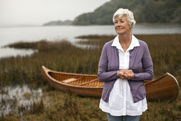 Mature woman looks away as she stands with her hands clasped posing for a portrait in front of a wooden canoe on a lakeshore.