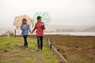 Two young girls hold hands as they carry open umbrellas and walk along a grassy path near a marshy shore.