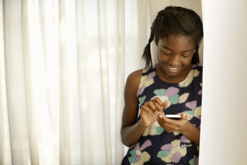 Smiling teenage girl texting on a smart phone.