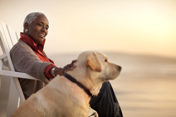 Smiling senior woman petting her dog while sitting on a beach.