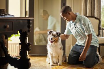Smiling teenage boy petting a dog.