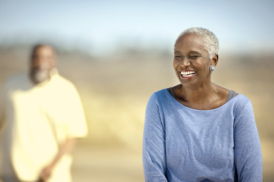 Smiling senior couple happily standing on a beach.