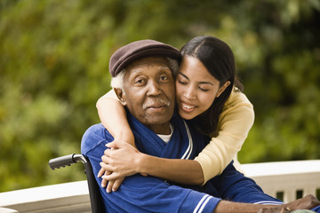Young woman leans over and embraces her grandfather sitting in a wheelchair as they pose for a portrait on a porch.