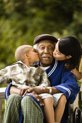 Senior man sitting in wheelchair is kissed on the cheek by his grandson sitting in his lap and on the other cheek by a young woman leaning over his shoulder as they pose for a portrait on a porch.