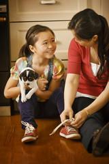 Mother helping her daughter tie her shoelaces.