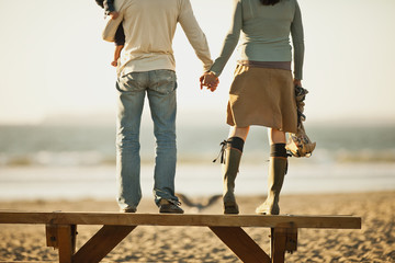 Young couple with baby hold hands whilst standing on a wooden bench looking out to sea.
