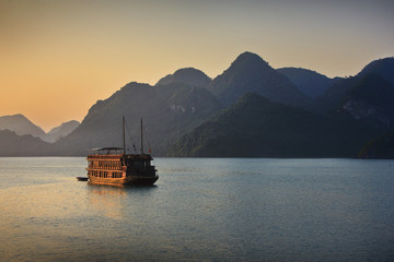 Boat on a sea surrounded by mountains in Vietnam.