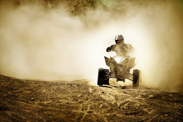 Quadbiker rides through dusty dirt road.