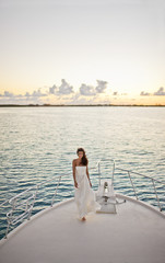 Portrait of a bride standing on the prow of a boat.
