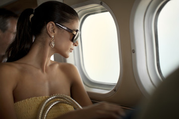 Content young woman looking out an airplane window.