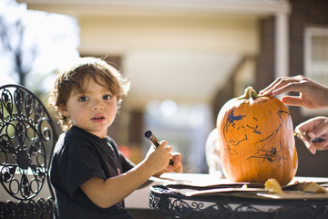 Father and son drawing face on pumpkin and carving Jack O' Lantern
