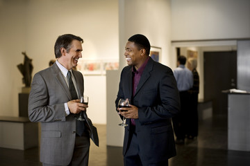 Business colleagues attend an art gallery opening.