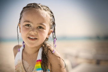 Portrait of a young girl with braided hair and sand on her face at the beach.