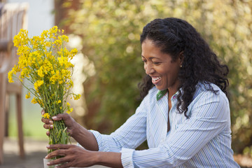 Happy mid adult woman putting a bunch of yellow flowers into a vase outdoors.
