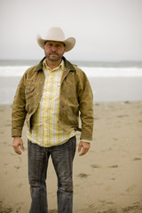 Portrait of a man standing on a beach wearing a cowboy hat.