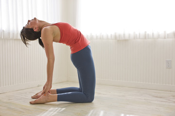 Mid-adult woman holding a yoga pose in a bare room inside her home.