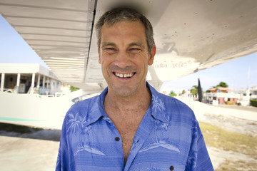Portrait of a grinning mature man standing underneath the wing of an airplane.