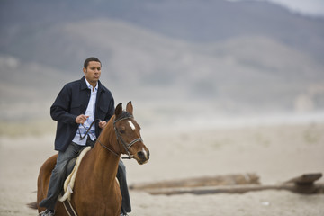 Mid-adult man riding a brown horse along a remote beach.